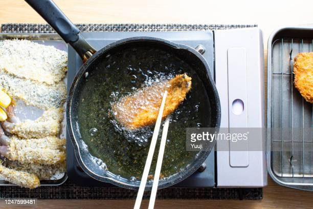 recipes for japanese home cooking, fried horse mackerel and fried shrimp.they're frying the horse mackerel in oil. - trachurus stock pictures, royalty-free photos & images
