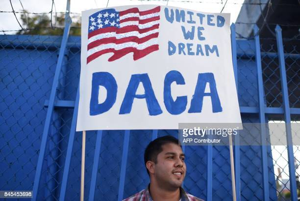 DACA recipient and appliance repair business owner Erick Marquez holds a sign during a protest in support of DACA which provides protection from...