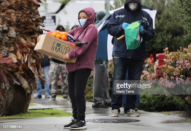 Recipient carries a box of food as others wait in line at a Food Bank distribution for those in need as the coronavirus pandemic continues on April...