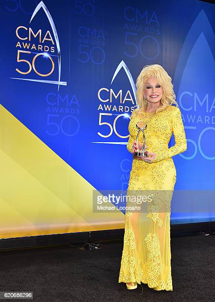 Recipient of the Willie Nelson Lifetime Achievement Award Dolly Parton poses backstage the 50th annual CMA Awards at the Bridgestone Arena on...