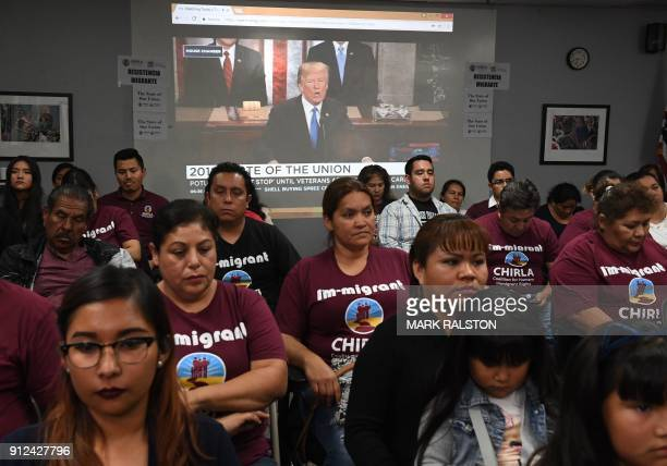 TOPSHOT DACA recipients and their supporters turn their back on US President Donald Trump as he talks about unity during a State of the Union party...