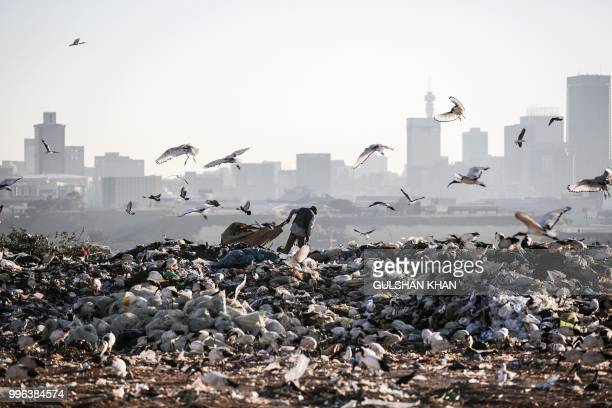A reclaimer wades through the waste at Robinson Deep landfill Johannesburg's largest landfill on June 29 2018
