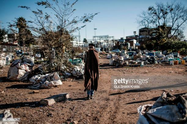 TOPSHOT Reclaimer walks through Mai Mai recyclers standing area where many reclaimers park their trolleys and separate the waste in Johannesburg on...