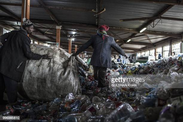 Reclaimers empty a bag of plastic bottles at Mudimu Recycling a buy back centre in Selby Johannesburg where reclaimers bring waste to be weighed and...