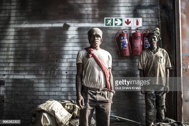 TOPSHOT Reclaimers Micheal Morosi and Johannes Matona pose for a picture at Mudimu Recycling a buy back centre in Selby Johannesburg where reclaimers...