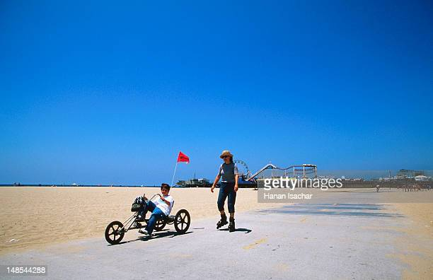 Recliner bike and rollerblader on path at Santa Monica Beach.