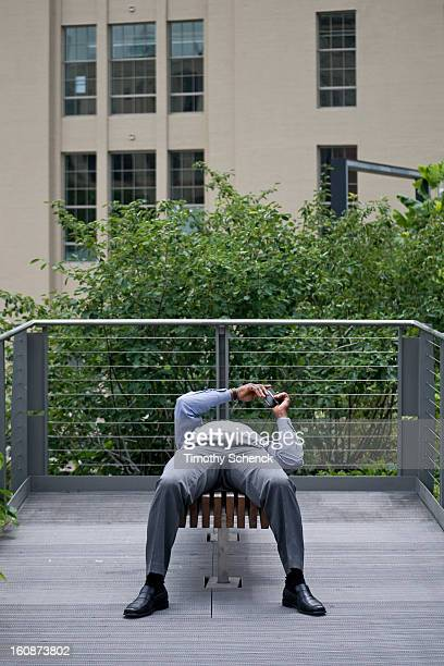 CONTENT] A reclining man relaxes and texts while enjoying the High Line park Chelsea NYC June 2012