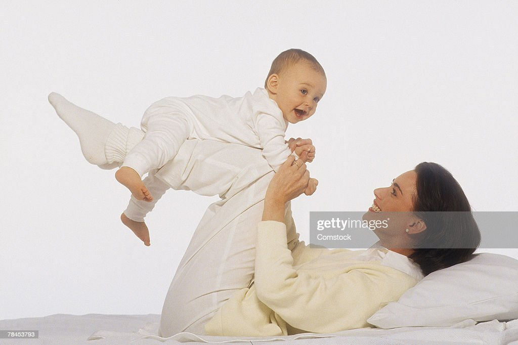 Reclining mother balancing baby on her legs : Stockfoto