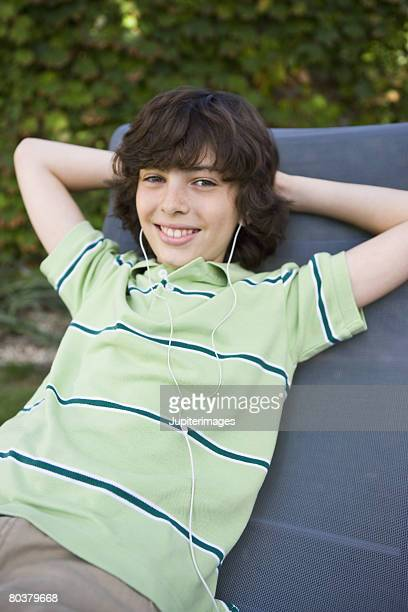 reclining preteen boy with earbuds - only boys stock pictures, royalty-free photos & images
