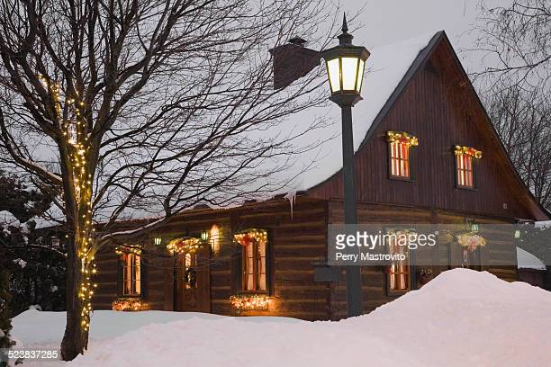 Reconstructed 1840s residential log home with Christmas decorations at dusk, Quebec, Canada