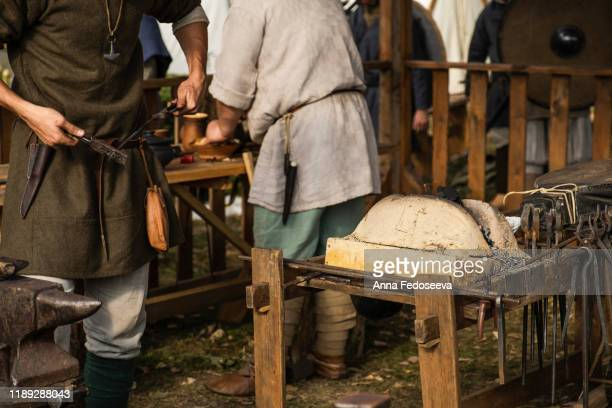 reconstruction of old crafts. a craftsman in historical clothing bends an iron rod with metal tongs. a blacksmith forges a metal product. dressed in an old outfit. ancient metallurgy. - rpg maker stock pictures, royalty-free photos & images