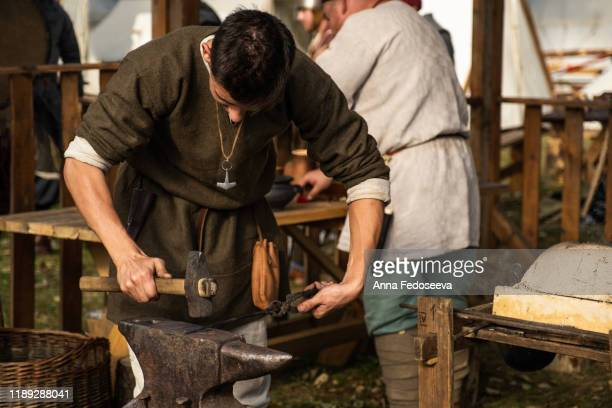reconstruction of old crafts. a craftsman in historical clothing is hammering on the anvil. a blacksmith forges a metal product. dressed in an old outfit. - historical reenactment stock pictures, royalty-free photos & images