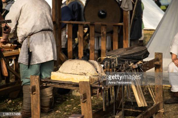 reconstruction of the forge. old crafts. craftsmen rest from work. blacksmith furs. metal tools. blacksmith forge. medieval historical role-playing games. dressed in an old outfit. bugle. - rpg maker stock pictures, royalty-free photos & images