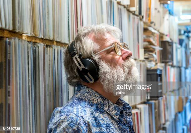 record collector with headset on, in front of his collection - ver a hora imagens e fotografias de stock
