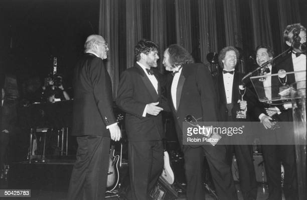 Record producer Ahmet Ertegun smiling while former members of the Byrds receive awards David Crosby Chris Hillman Gene Clark Mike Clarke speaking...
