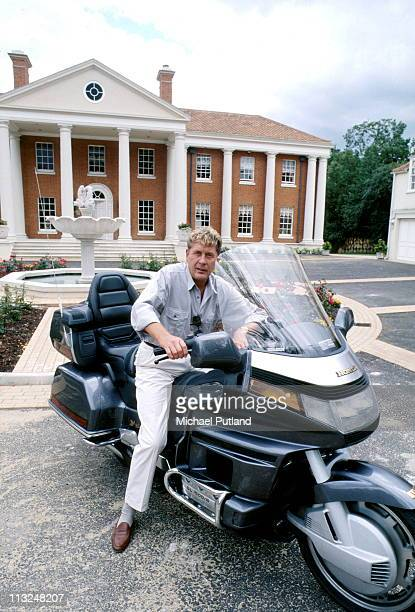 Record producer and songwriter Mickie Most portrait on a Honda motorbike at home in Totteridge London circa 1988