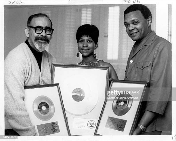 Record producer Jerry Wexler soul singer Aretha Franklin and her husband and manager Ted White pose for a portrait holding framed records that were...