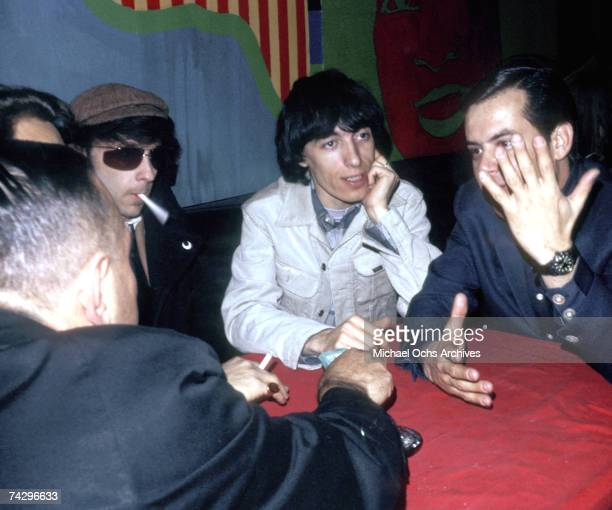 """Record producer Phil Spector sits at a table with bassist Bill Wyman of the rock and roll band """"The Rolling Stones"""" in circa 1966."""