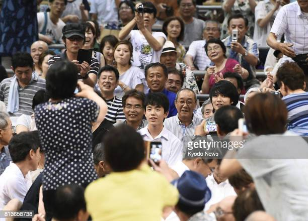 Recordbreaking pro shogi Japanese chess player Sota Fujii draws attention from the crowd during his visit to the Nagoya Grand Sumo Tournament at...
