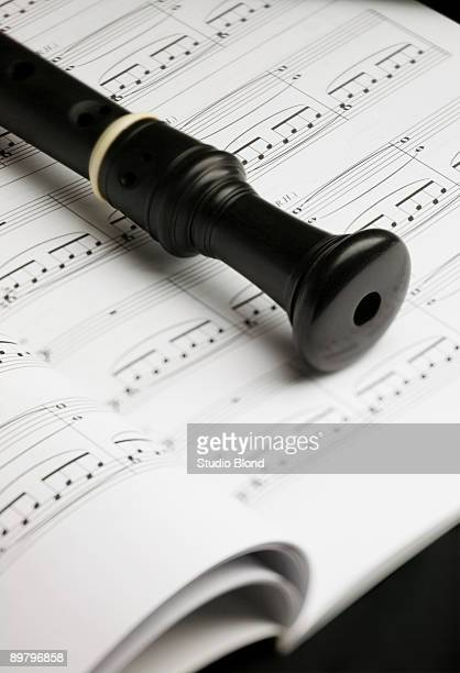 a recorder lying on a book of sheet music - recorder musical instrument stock photos and pictures