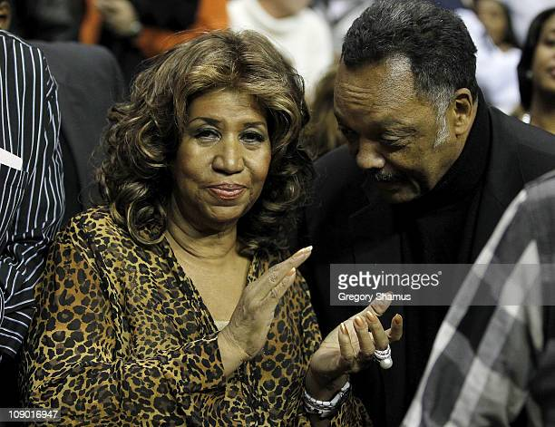 Recording artist Aretha Franklin looks on with cilvil rights leader Jesse Jackson while the Detroit Pistons play the Miami Heat at The Palace of...
