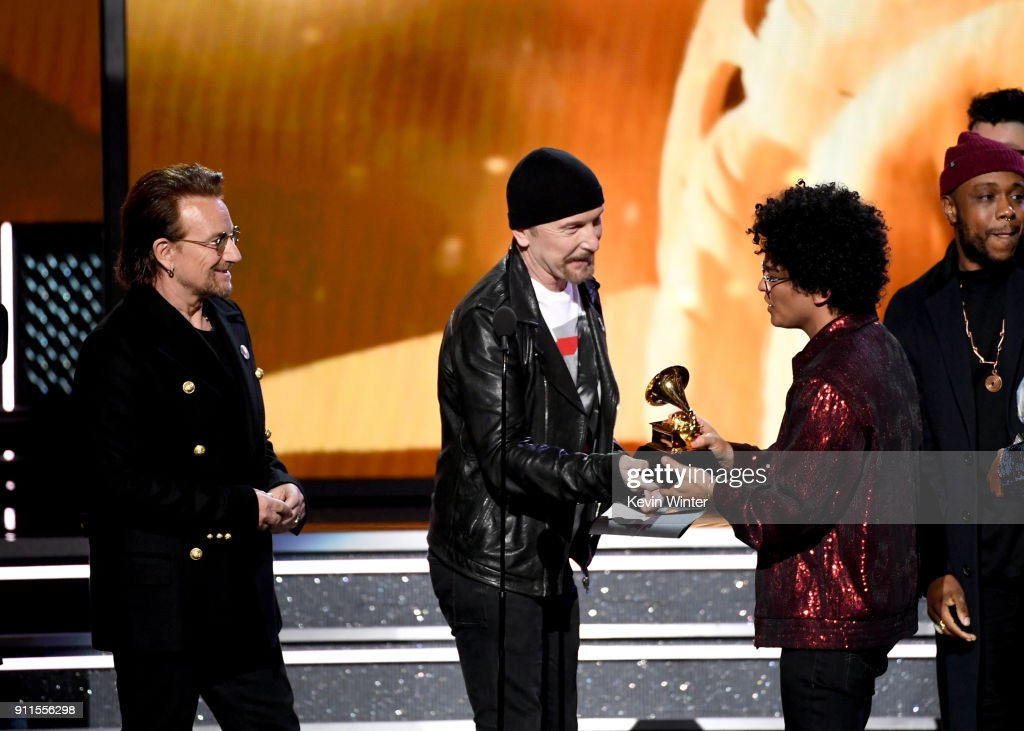 Recording artist Bruno Mars (R) accepts Album of the Year for '24K Magic' from Bono (L) and The Edge (C) of music group U2 onstage during the 60th Annual GRAMMY Awards at Madison Square Garden on January 28, 2018 in New York City.