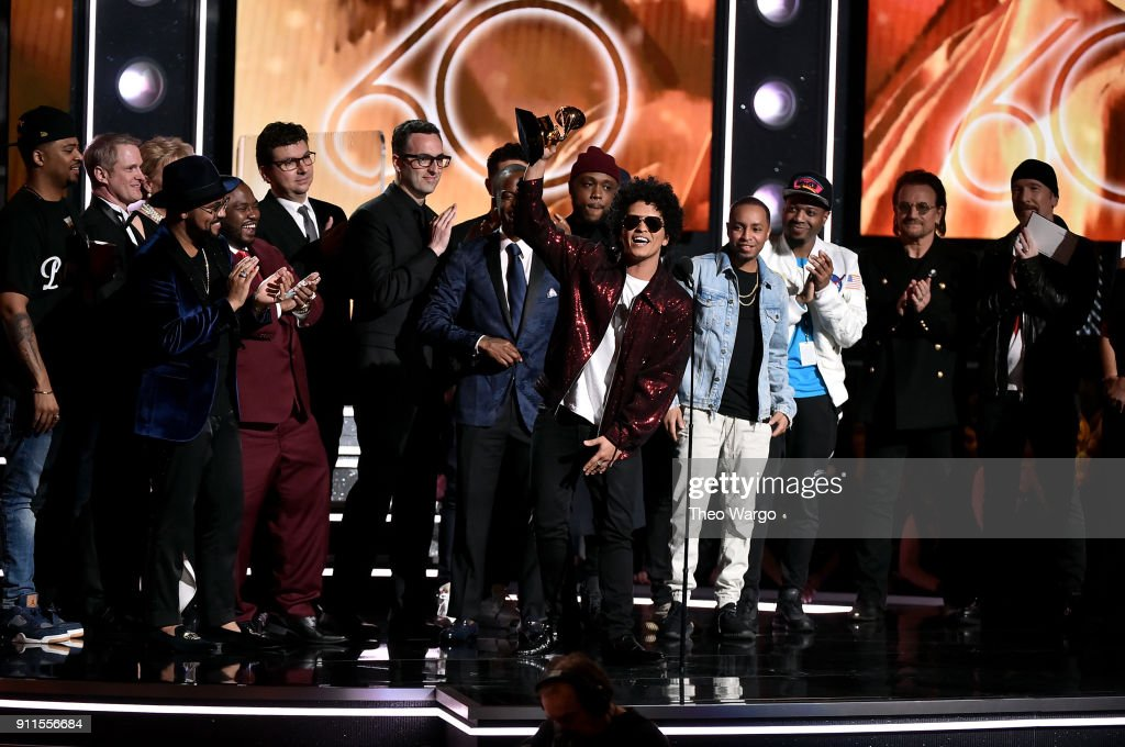 Recording artist Bruno Mars (holding GRAMMY award trophy) and production team accept the Album Of The Year award for '24K Magic' from recording artists Bono (2nd from R) and The Edge (R) of musical group U2 onstage during the 60th Annual GRAMMY Awards at Madison Square Garden on January 28, 2018 in New York City.