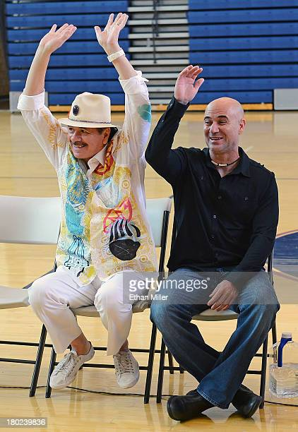 Recording artist Carlos Santana and former tennis player Andre Agassi joke around as they visit the Andre Agassi College Preparatory Academy to...
