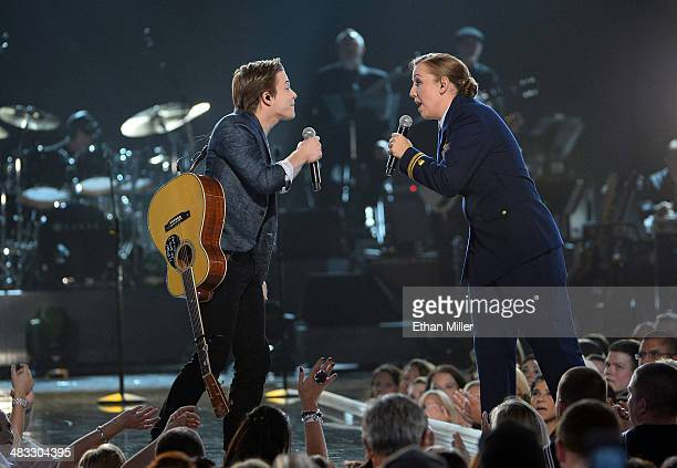 Recording artist Hunter Hayes and Coast Guard Lt. J.g. Katie Spira perform onstage during ACM Presents: An All-Star Salute To The Troops at the MGM...