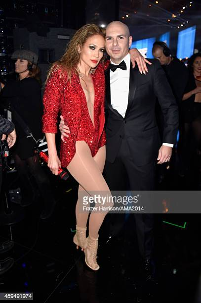 Recording artist Jennifer Lopez and host Pitbull pose backstage at the 2014 American Music Awards at Nokia Theatre LA Live on November 23 2014 in Los...