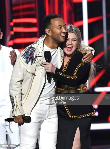 Recording artist John Legend and host Kelly Clarkson embrace onstage during the 2018 Billboard Music Awards at MGM Grand Garden Arena on May 20 2018...