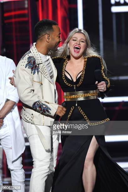 Recording artist John Legend and host Kelly Clarkson speak onstage during the 2018 Billboard Music Awards at MGM Grand Garden Arena on May 20 2018 in...