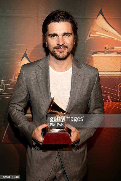 Recording artist Juanes poses with the Best Pop/Rock Album award for 'Loco de Amor' backstage at the 15th annual Latin GRAMMY Awards premiere...
