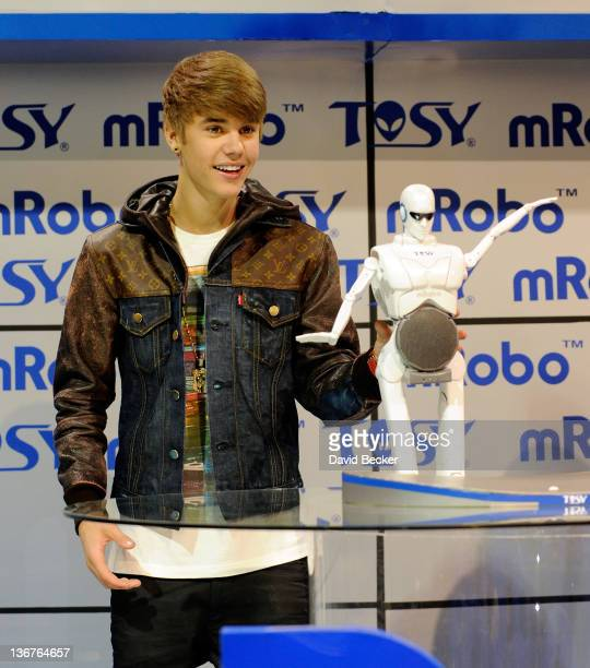 Recording artist Justin Bieber displays an mRobo Ultra Bass robot toy that was unveiled at the Tosy booth at the 2012 International Consumer...