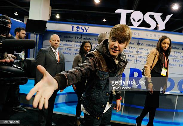 Recording artist Justin Bieber greets members of the press before an unveiling of the mRobo Ultra Bass robot toy at the Tosy booth at the 2012...