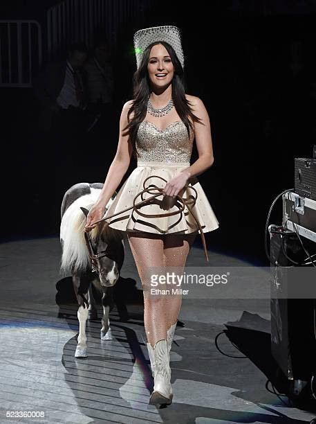 Recording artist Kacey Musgraves walks to the stage with a miniature horse named Mamacita as she opens for George Strait during the first of his...