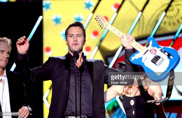 Recording artist Luke Bryan accepts the award for Artist of the Year from presenter Joe Buck onstage during the American Country Awards 2013 at the...