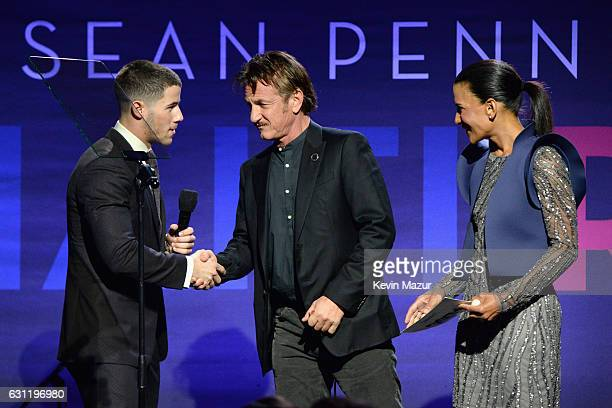 Recording artist Nick Jonas cohost Sean Penn and Sotheby's Americas EVP/Chairman Andrea Fiuczynski speak onstage during the 6th Annual Sean Penn...