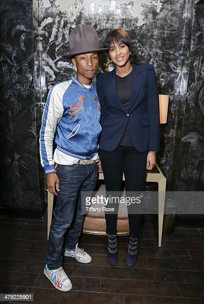 Recording artist Pharrell Williams and Helen Lasichanh attend VIOLET GREY Honors Elizabeth Taylor At She's So Violet Salon Dinner on February 26 2014...