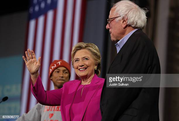 Recording artist Pharrell Williams Democratic presidential nominee Hillary Clinton and US Sen Bernie Sanders greet supporters during a campaign rally...