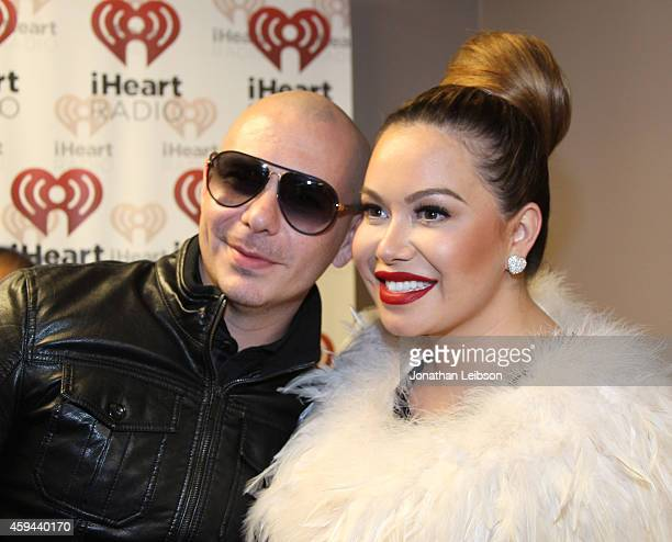 Recording artist Pitbull and singer Chiquis Rivera pose backstage during the iHeartRadio Fiesta Latina festival presented by Sprint at The Forum on...