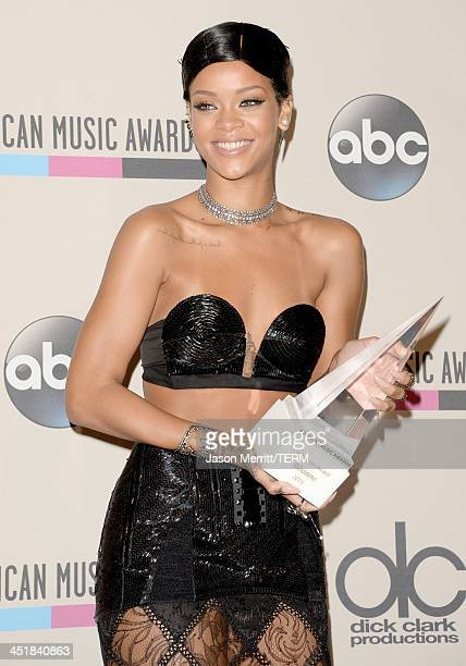 Recording artist Rihanna poses with the Icon Award in the press room during the 2013 American Music Awards at Nokia Theatre LA Live on November 24...