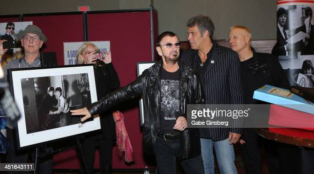 Recording artist Ringo Starr explains a photo he took to musician Mark Rivera and drummer Gregg Bissonette at a photo exhibition of Starr's...