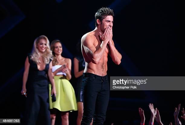 Recording artist Rita Ora and actress Jessica Alba watch as actor Zac Efron accepts the Best Shirtless Performance award for 'That Awkward Moment'...