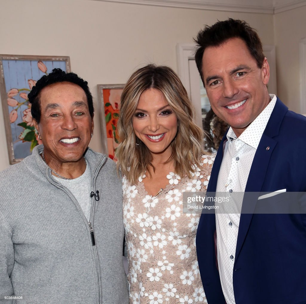 Recording artist Smokey Robinson poses with hosts Debbie Matenopoulos and Mark Steines at Hallmark's 'Home & Family' at Universal Studios Hollywood on February 23, 2018 in Universal City, California.