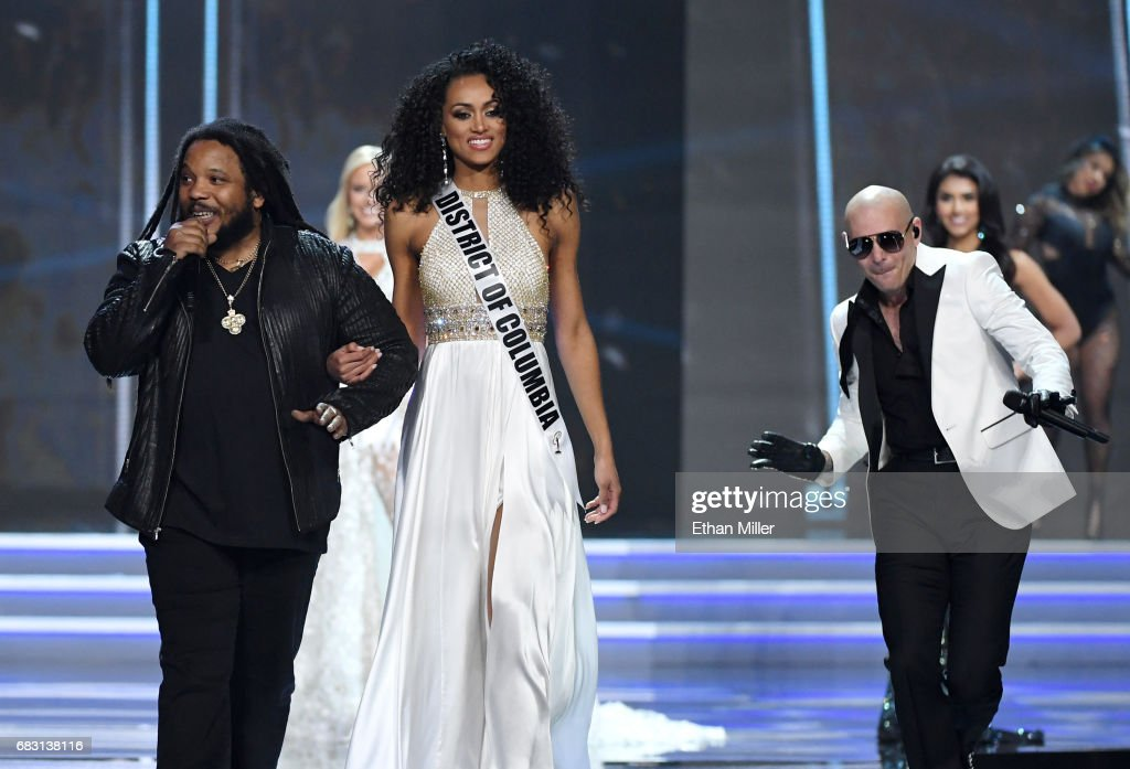 Recording artist Stephen Marley sings while escorting Miss District of Columbia USA 2017 Kara McCullough onstage as rapper Pitbull performs during the 2017 Miss USA pageant at the Mandalay Bay Events Center on May 14, 2017 in Las Vegas, Nevada. McCullough went on to be named the new Miss USA.