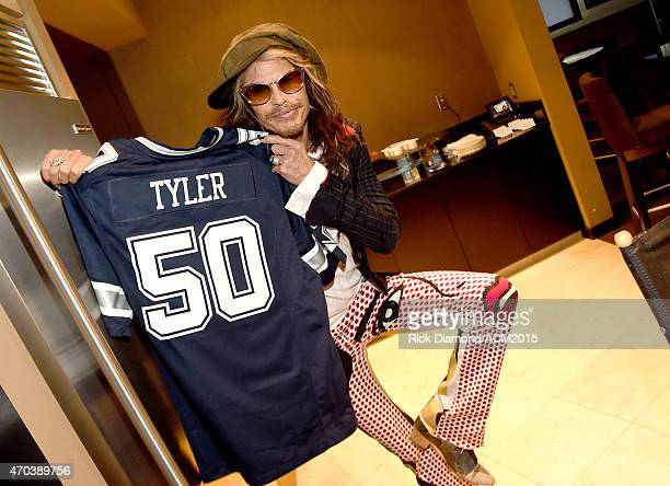 Recording artist Steven Tyler poses with a football jersey backstage at the 50th Academy of Country Music Awards at ATT Stadium on April 19 2015 in...
