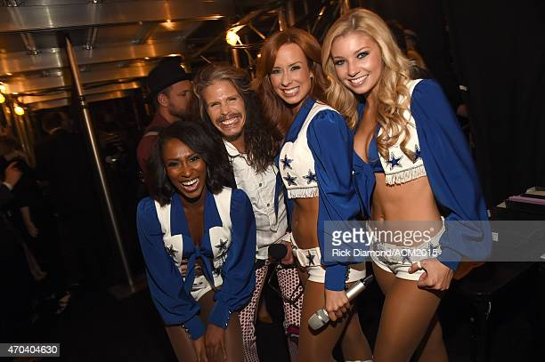 Recording artist Steven Tyler poses with Dallas Cowboys Cheerleaders backstage during the 50th Academy of Country Music Awards at ATT Stadium on...