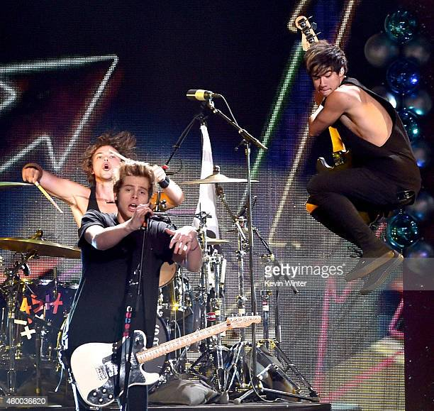 Recording artists Ashton Irwin Luke Hemmings and Calum Hood of music group 5 Seconds of Summer perform onstage during KIIS FM's Jingle Ball 2014...