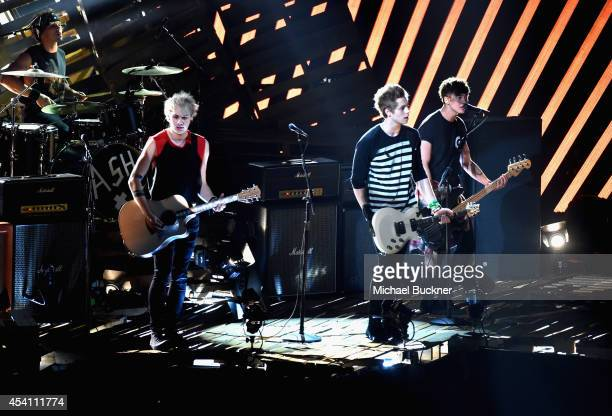 Recording artists Ashton Irwin, Michael Clifford, Luke Hemmings, and Calum Hood of 5 Seconds of Summer perform onstage during the 2014 MTV Video...